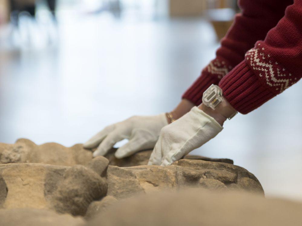 Hände tasten ein Museums-Objekt aus Stein