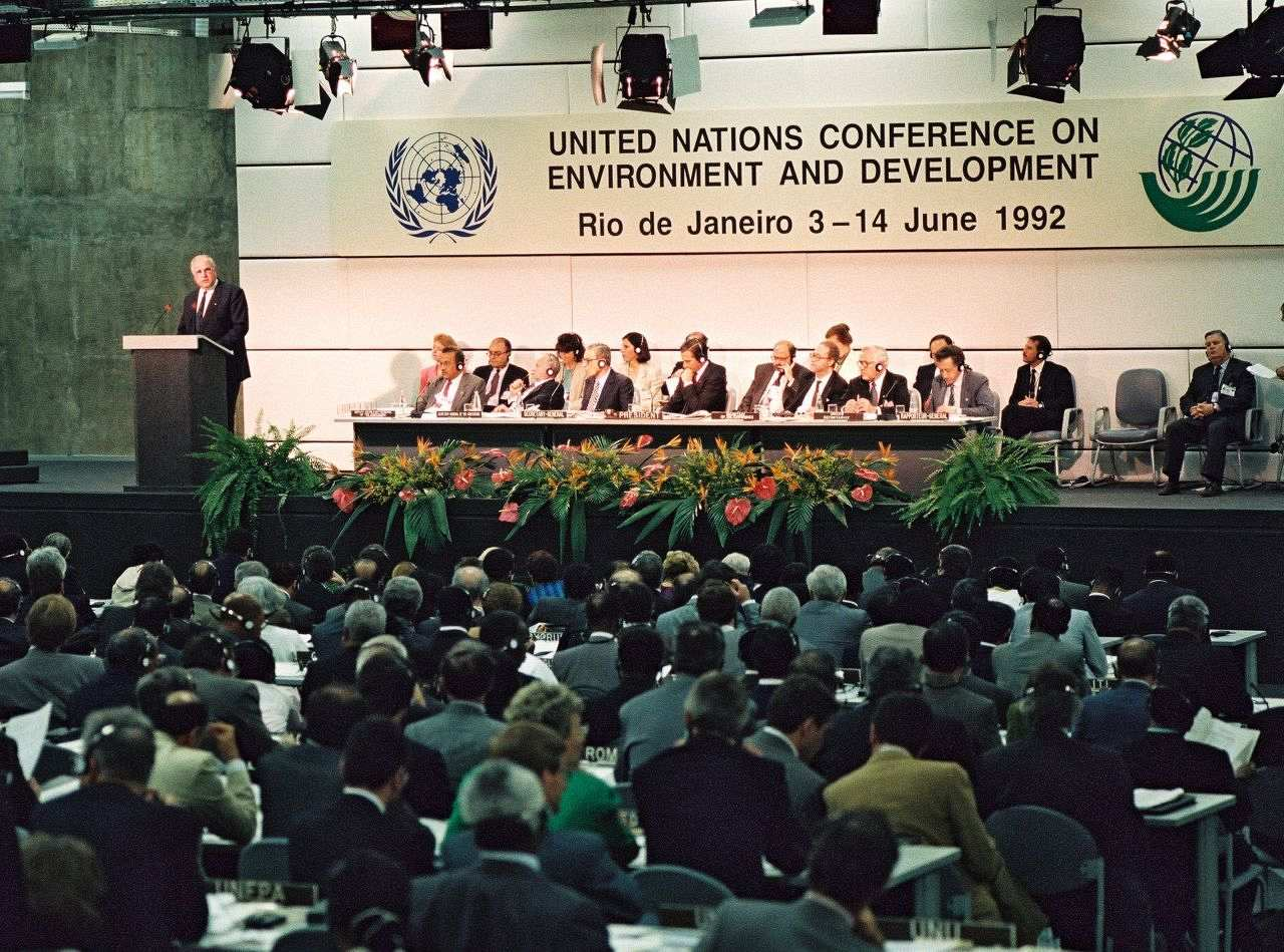 Farb-Foto, Helmut Kohl hinter Redner-Pult auf einer Tribüne, rechts davon Tisch mit weiteren Delegierten. Hinter ihnen ein Schild, darauf: 'United Nations Conference on Environment and Development, Rio de Janeiro 3-14 June 1992'. Publikum sitzt an Tischen.