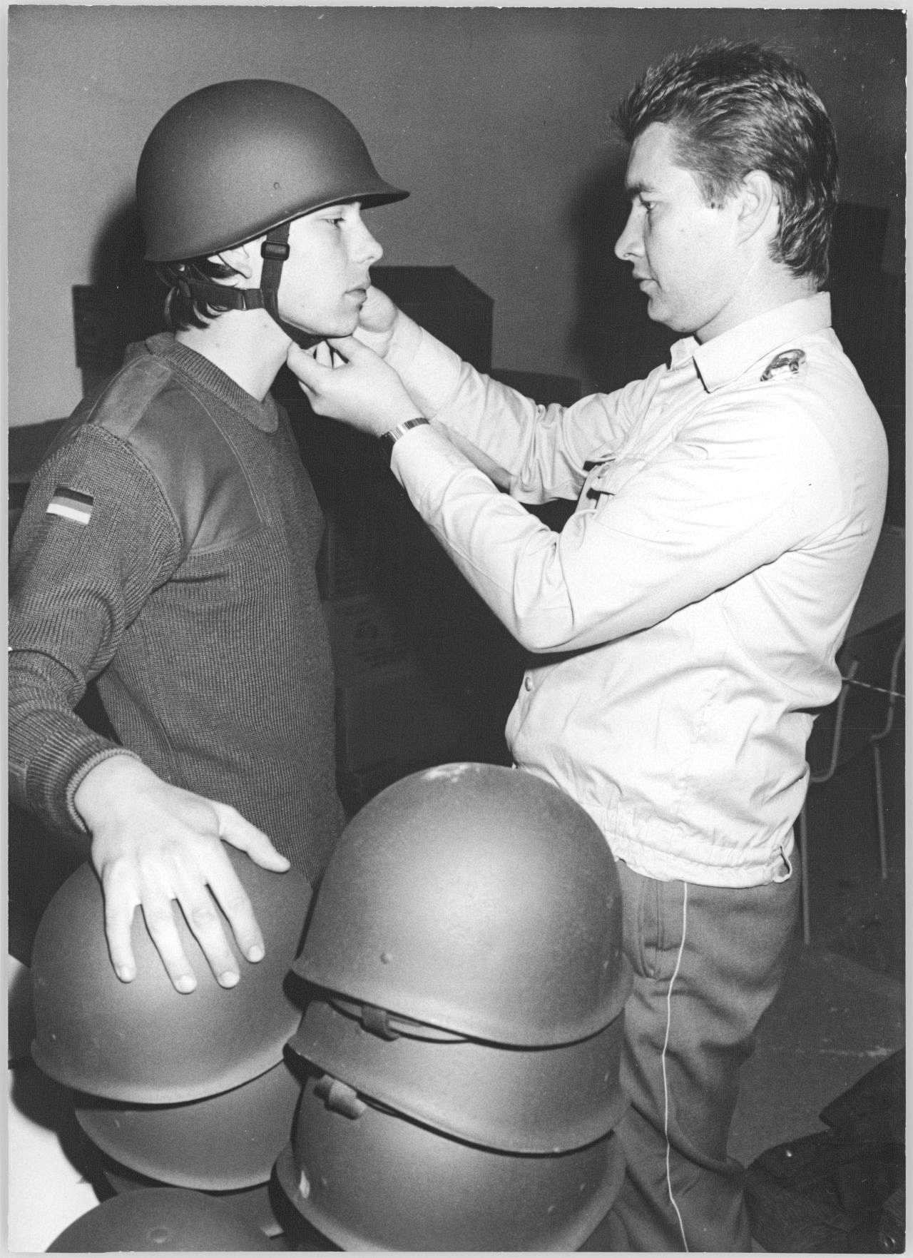 schwarzweiße Fotografie, Hochformat: Ein junger Soldat der NVA, links im Bild, erhält seine neue Bundeswehr-Uniform. Ein Soldat der Bundeswehr, rechts im Bild, legt ihm den Helm an.