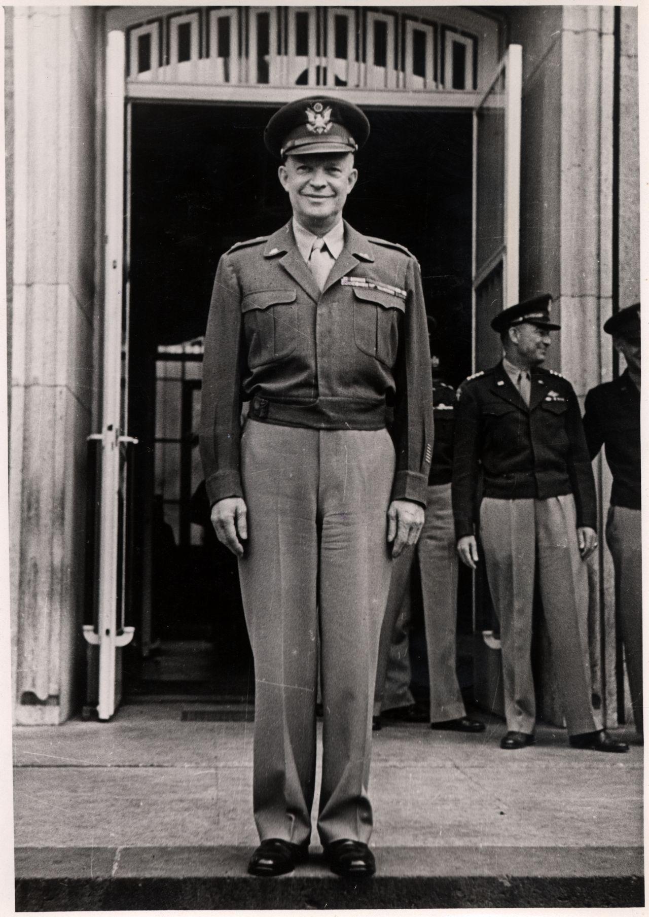 Eisenhower steht in Militäruniform lächelnd vor auf den Stufen vor einer geöffneten Flügeltür.
