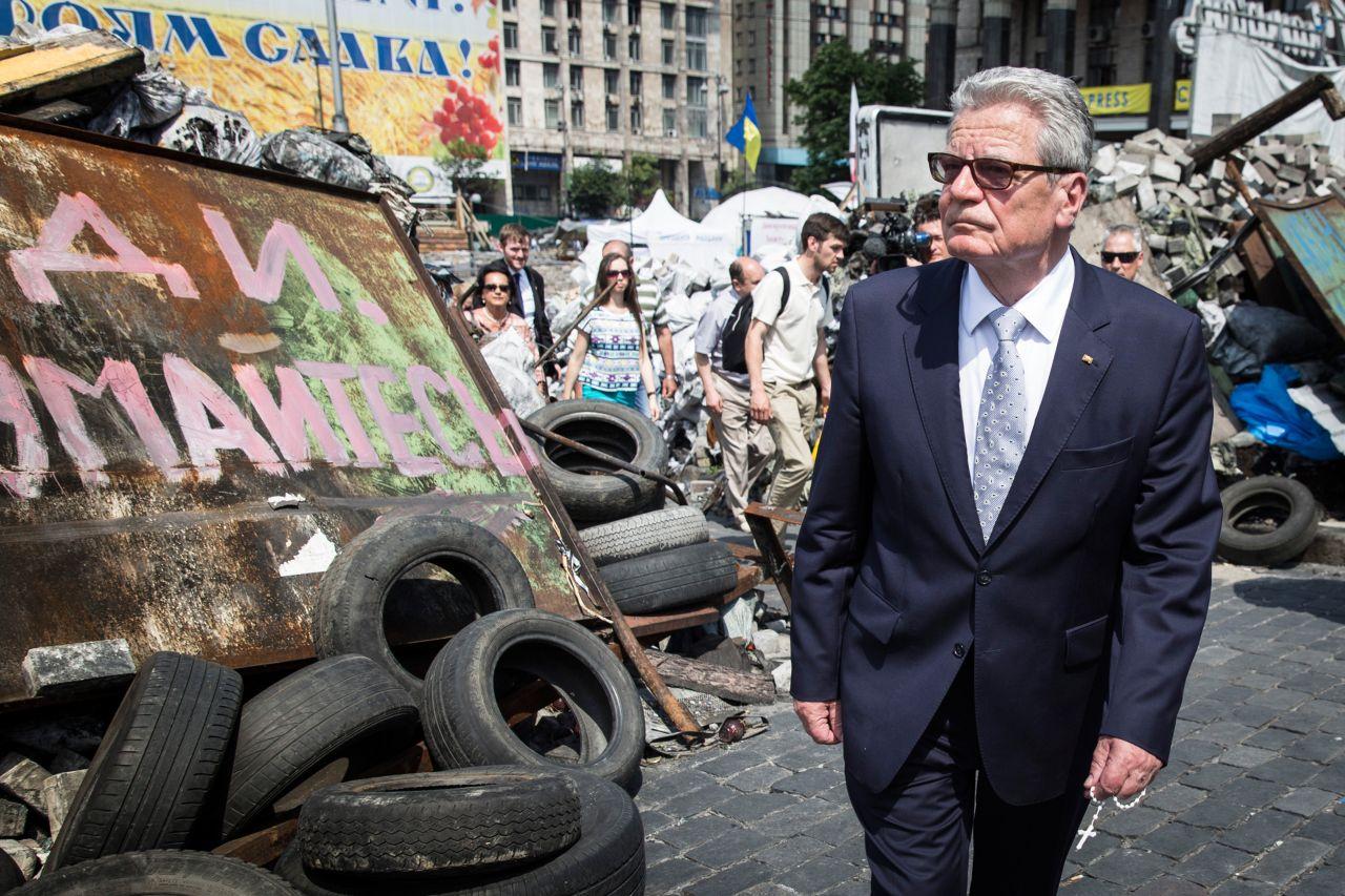 arbiges Foto: Bundespräsident Joachim Gauck mit Sonnenbrille und Rosenkranz in der linken Hand. Er geht vor Straßenbarrikaden, die unter anderem aus Reifen, Schildern und aufgeschütteten Ziegeln bestehen und teils mit Graffitis in kyrillischen Schriftzeic