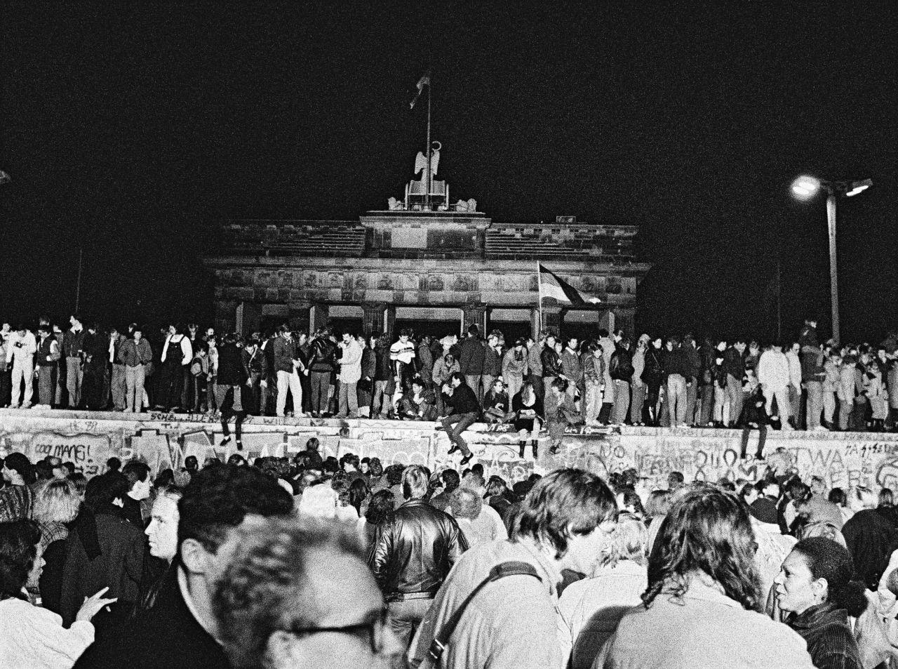 Foto von feiernden Menschen auf und vor der Berliner Mauer bei Nacht. Zentral im Bild ist das Brandenburger Tor hinter der Mauer zu sehen.