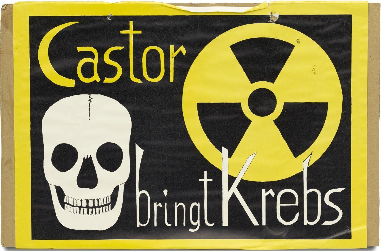 Auf brauner Pappe aufgeklebtes schwarzgrundiges Blatt mit gelber Umrandung; unten links Totenschädel, oben rechts Symbol für Radioaktivität; Text oben links 'Castor' und unten rechts 'bringt Krebs'. Am Rand oben zwei Löcher mit einer durchgezogenen Kordel