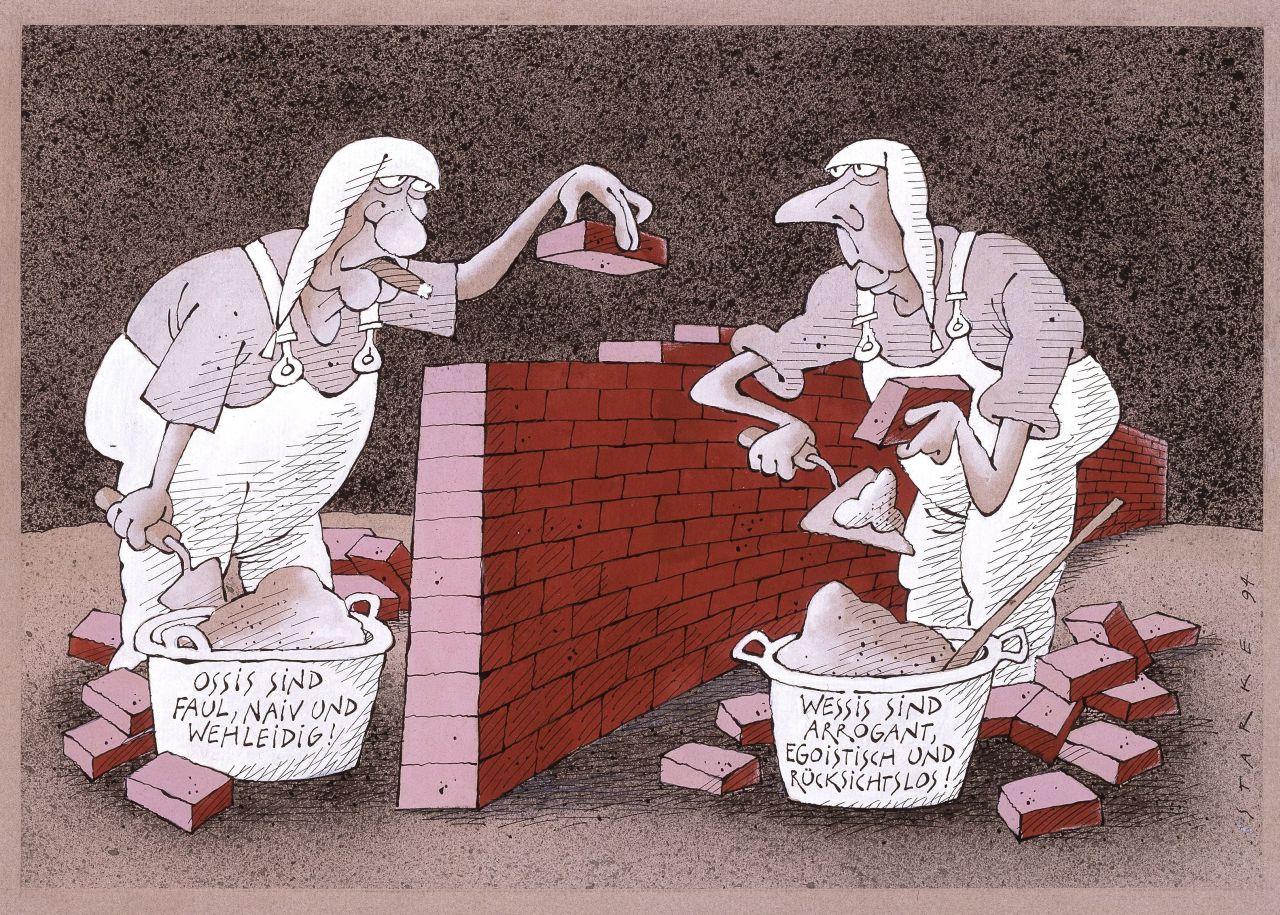 Schwarz-weiße Abbildung von zwei deutschen Micheln als Maurer. Sie mauern eine Mauer mit roten Steinen - diese sind der einzige farbige Bestandteil der Karikatur. Der linke Maurer hat eine Zigarre im Mund und sein Mörtelkübel trägt die Aufschrift: Ossis s