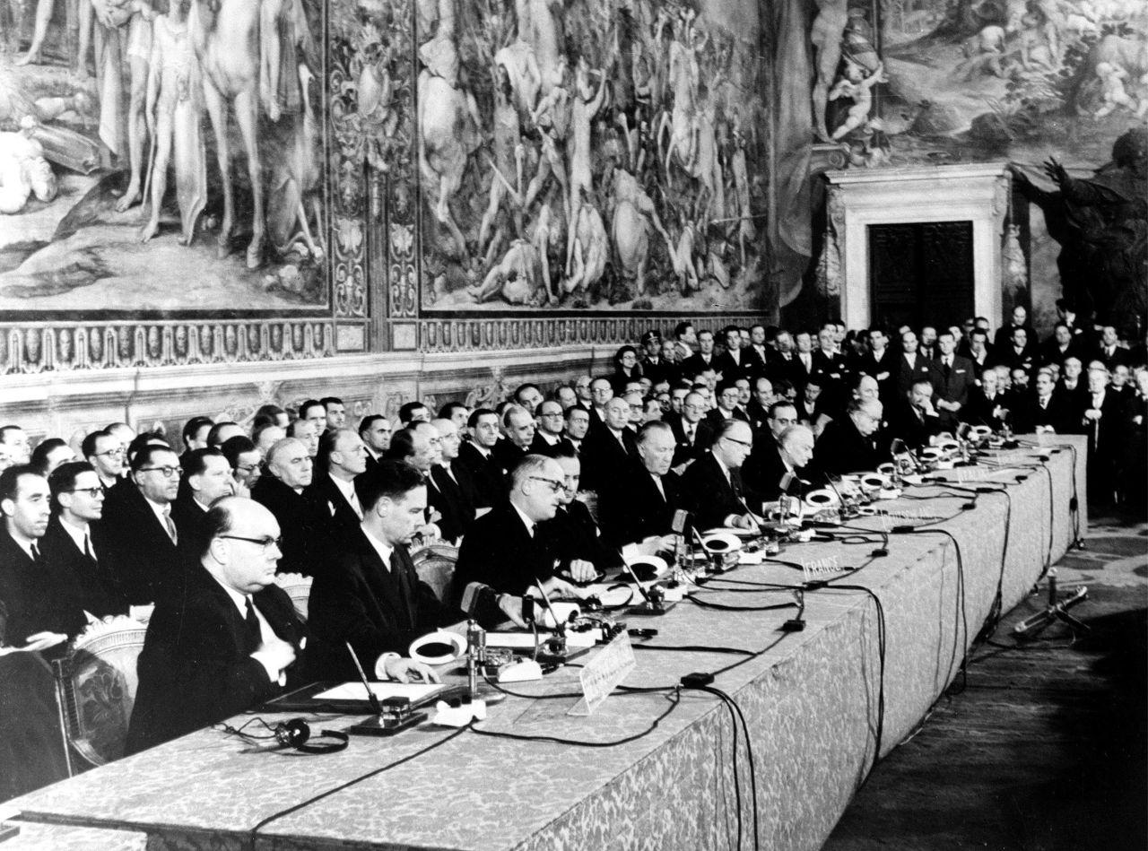 In einem Saal mit prächtiger Wandbemalung sitzen 11 Männer an einem langen Tisch mit Mikrofonen, Dokumenten und Füllfederhaltern
