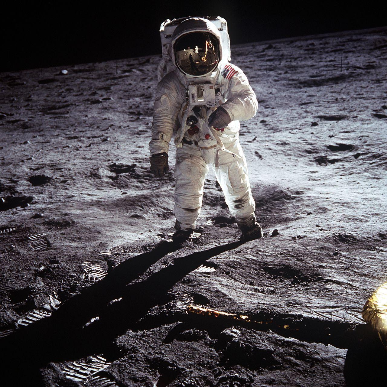 Der Astronaut Buzz Aldrin geht auf der unebenen Mondoberfläche. Er trägt einen weißen Raumanzug mit USA-Flagge auf der linken Schulter und mit einem nahezu kugelförmigen Helm.