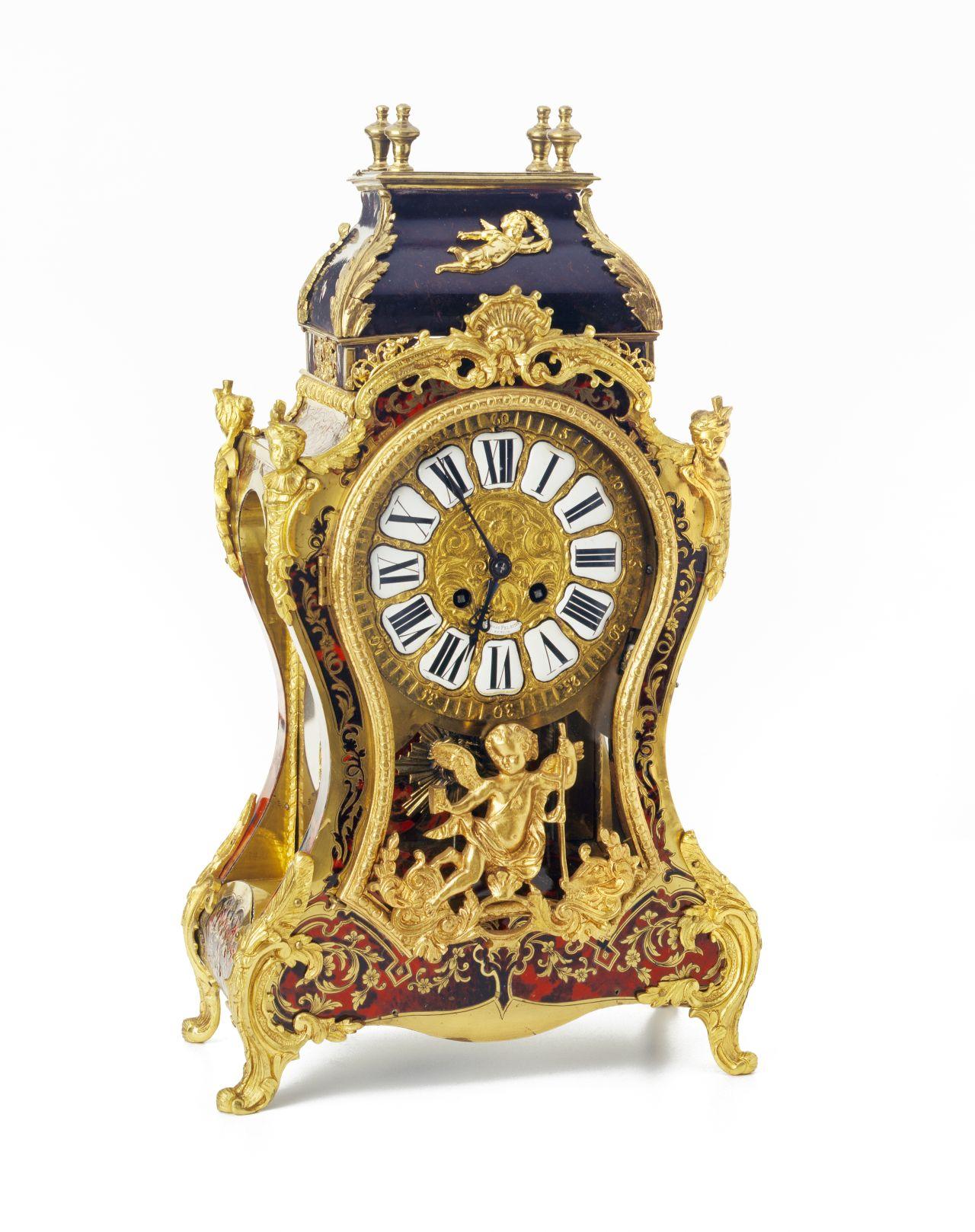 Antike Uhr in rotem Gehäuse mit goldenen Verzierungen